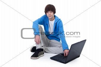 Casual teenager boy sitting on the floor