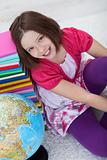Happy school girl with books and globe