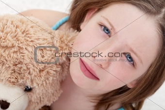 Sad girl holding teddy bear and crying
