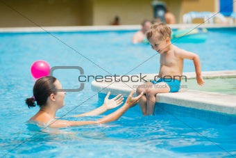 boy with mather playing in a pool of water