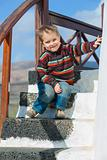 Happy little boy sitting on stairs