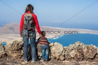 Back view mother and son standing on cliff's edge