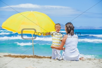 Boy and his mother with big umbrella