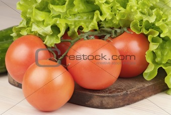 tomatoes and salad on cutting board on the table