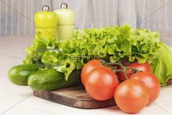 tomatoes, cucumbers and salad on cutting board on the table