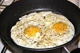 Spicy fried eggs in pan, sunny side up