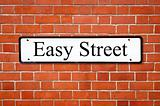 Easy street sign on a brick wall.
