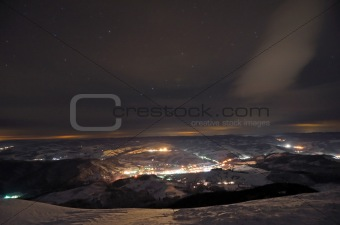 Small night town in the mountains under cloudy starry sky