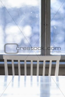 A white stool by the window and table
