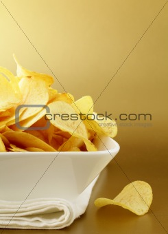 potato chips in a white bowl on a gold background