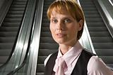 Businesswoman by escalators