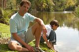 Father and son on riverbank