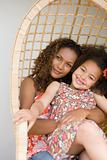 Mother and daughter in a wicker chair