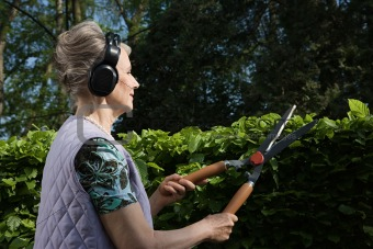 Woman wearing headphones and cutting hedge