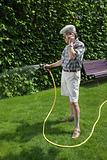 Man on cellphone whilst watering lawn