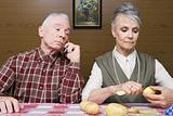 Man on cellphone as wife peels potatoes