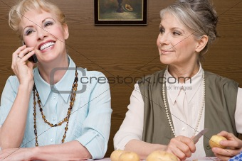 Senior women with cellphone and potatoes