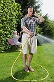 Man listening to headphones and watering lawn