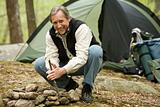 Mature man camping in a forest