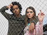 Two teenagers stood behind fence