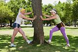 Two senior adult women warming up in the park