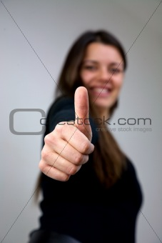 close up of young woman with thumb up smiling