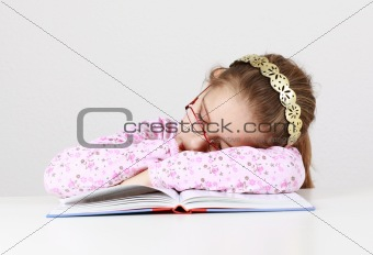Tired schoolgirl sleeping on book