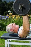 Senior adult man lifting barbell in park