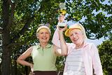 Two senior adult women lifting trophy