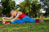 Senior adult woman stretching in park