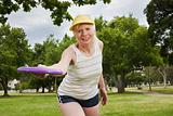 Senior adult woman playing frisbee in park