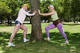 Two senior adult women stretching in park