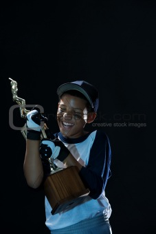Boy hugging a baseball trophy