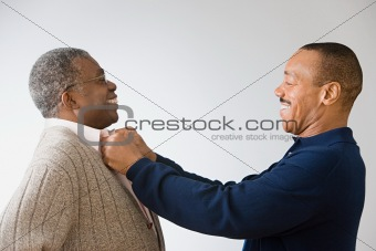 Son adjusting father's shirt