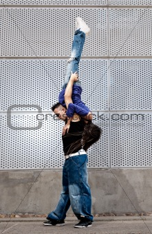 Young urban couple dancers hip hop dancing urban scene