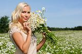 beautiful woman at the meadow with bunch of  chamomiles.