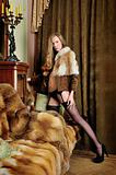 woman in fur coat  at the mirror in  Luxurious classical interior.