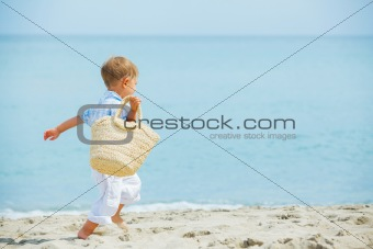 Boy with beach bag on tropical beach