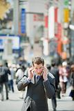 Businessman trying to listen to cell phone