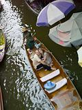 Couple in a boat by floating market