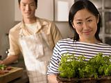 Couple in kitchen with herbs