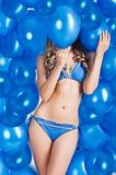 swimsuit and balloons in blue, her face is behind one balloon