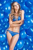 swimsuit and balloons in blue, she looks up at left