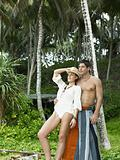 Couple standing by palm trees