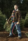 Man holding christmas tree and saw