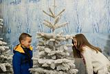 Boy and girl playing around christmas tree