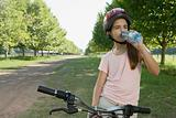 Girl on bike drinking water