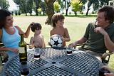 Boys with football and parents with wine