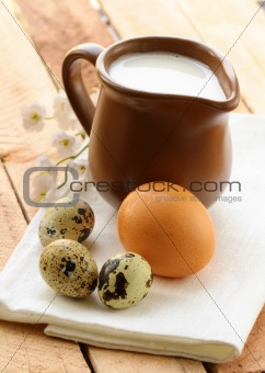 Ceramic jug with milk and eggs on a wooden table , rustic style