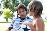 Boy with football talking to man